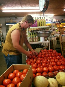 Austin Wilson stocks fresh tomatoes at Ferguson's Produce.