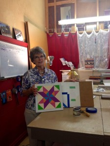 Shaaron Kohl, owner at the Red Rooster Emporium and coordinator for the McCormick Quilt Tour, displays a quilt panel, a piece of artwork in progress at the shop.